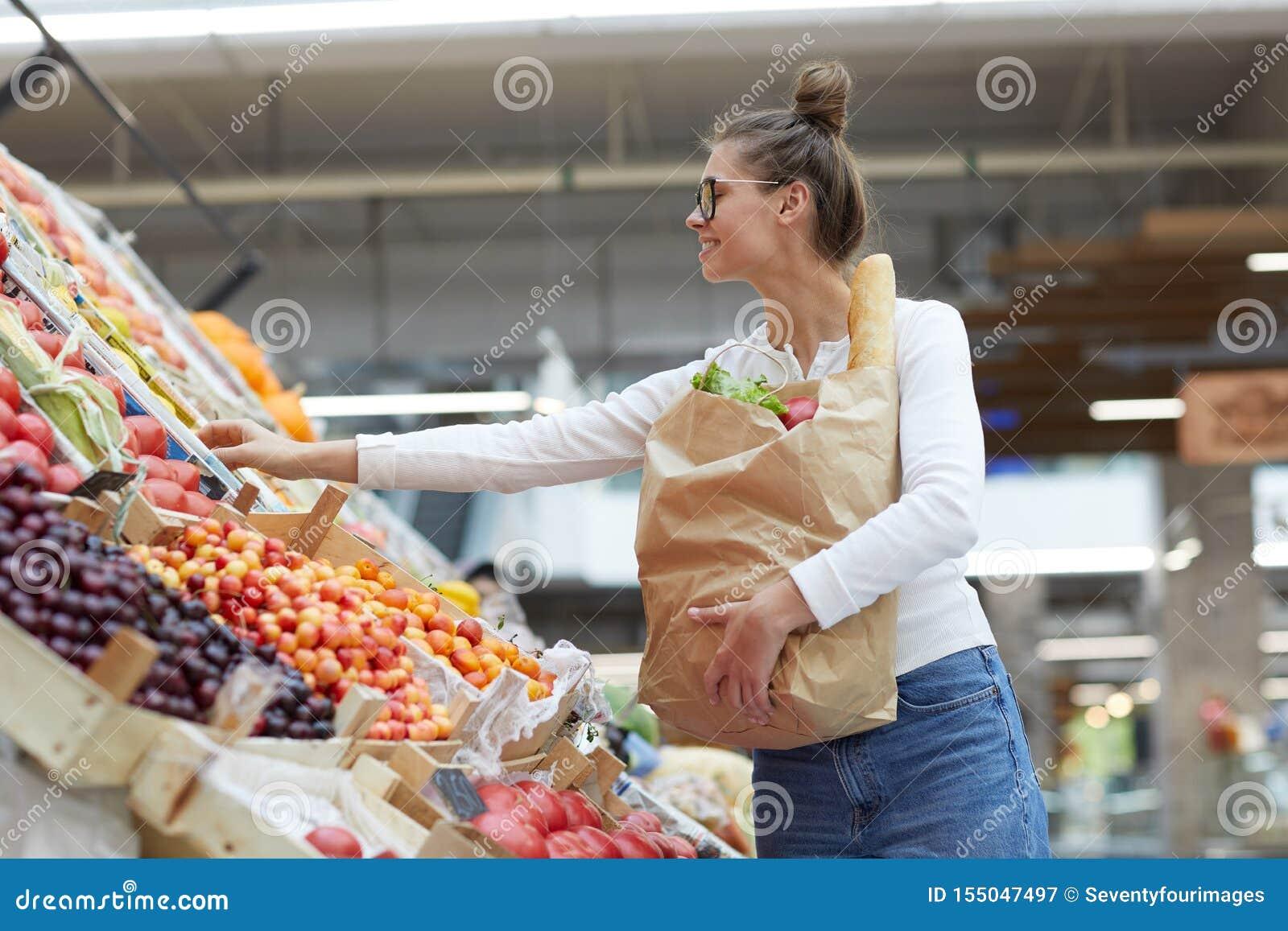 Młoda Kobieta przy Owocowym stojakiem