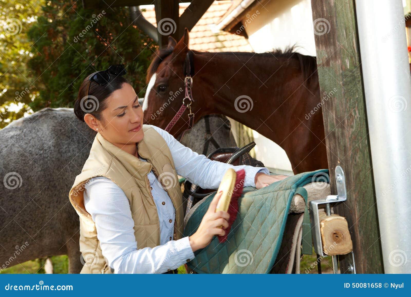 Młoda kobieta przygotowywa konia