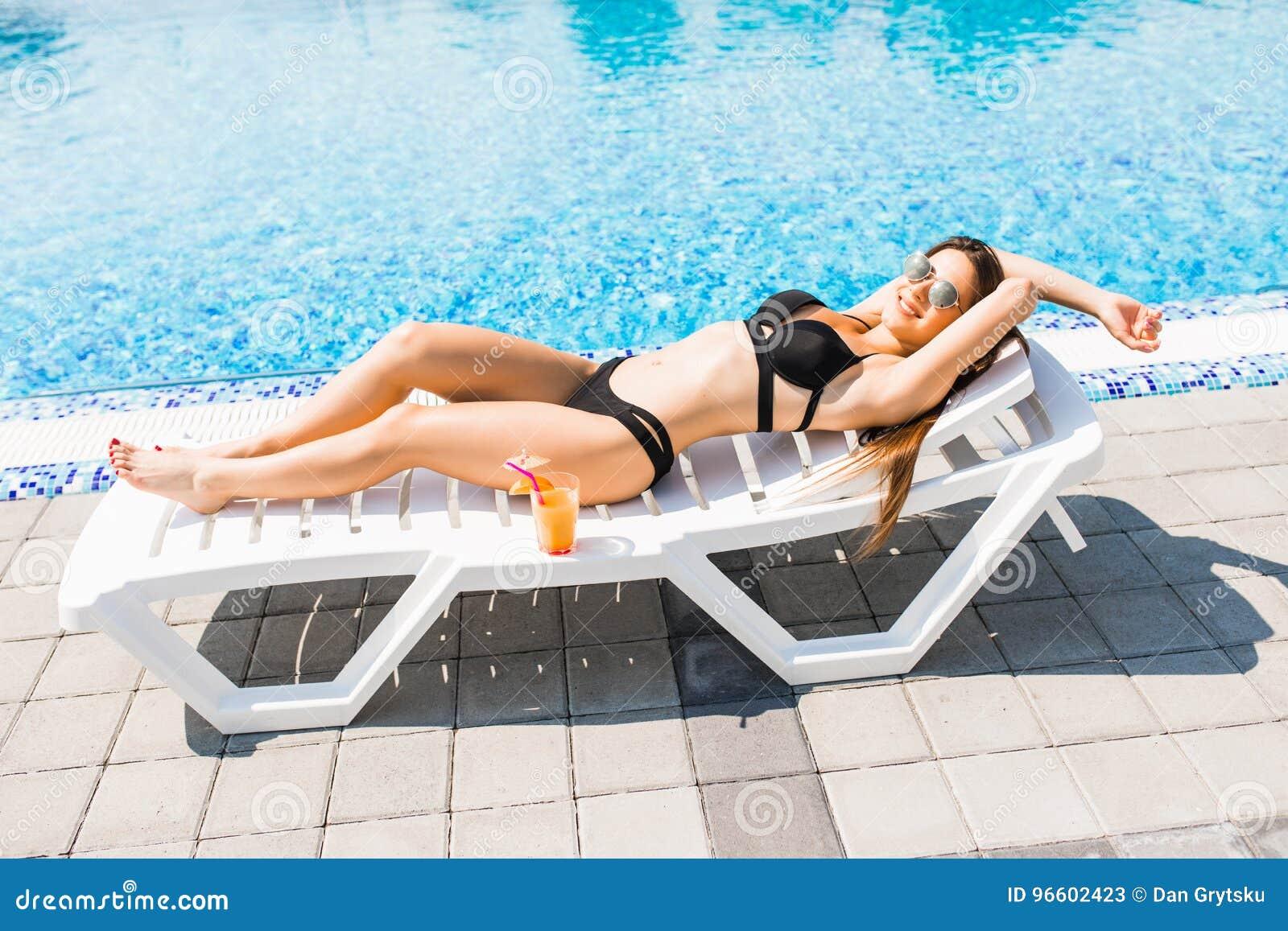 Młoda kobieta relaksuje z koktajlem na bryczki longue w swimsuit młodzi dorośli