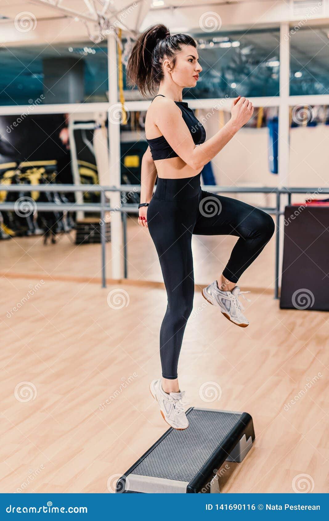 Młoda kobieta robi sprawności fizycznej ćwiczy w sprawności fizycznej centrum