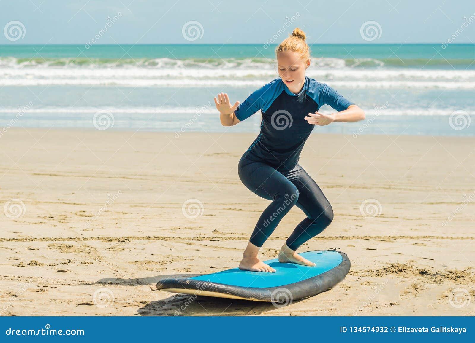 Młoda kobieta trenuje stać na kipieli przed pierwszy surfing lekcją