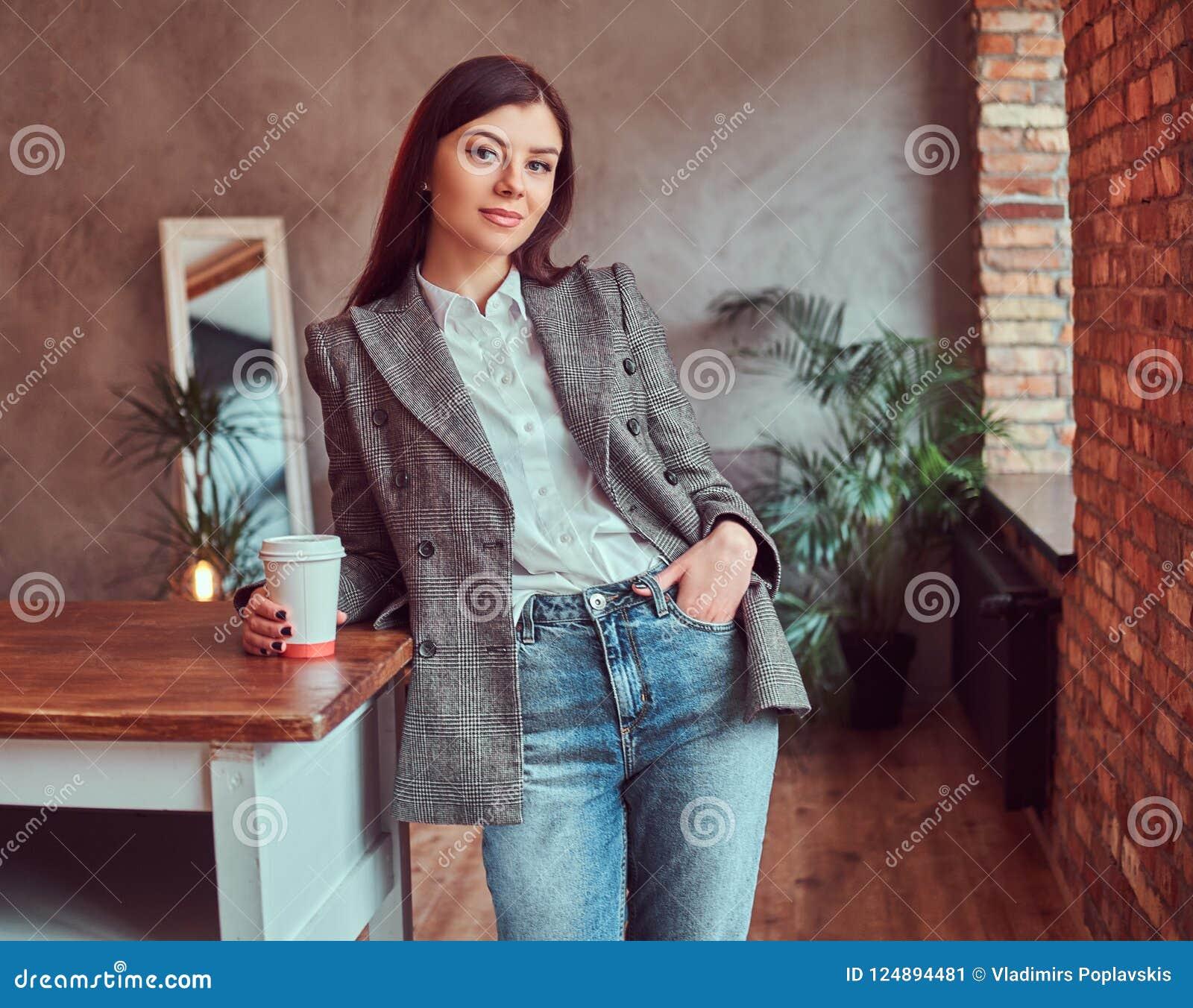 Młoda kobieta trzyma filiżankę takeaway kawa ubierał w szarej eleganckiej kurtce podczas gdy opierający na stole w pokoju z loft