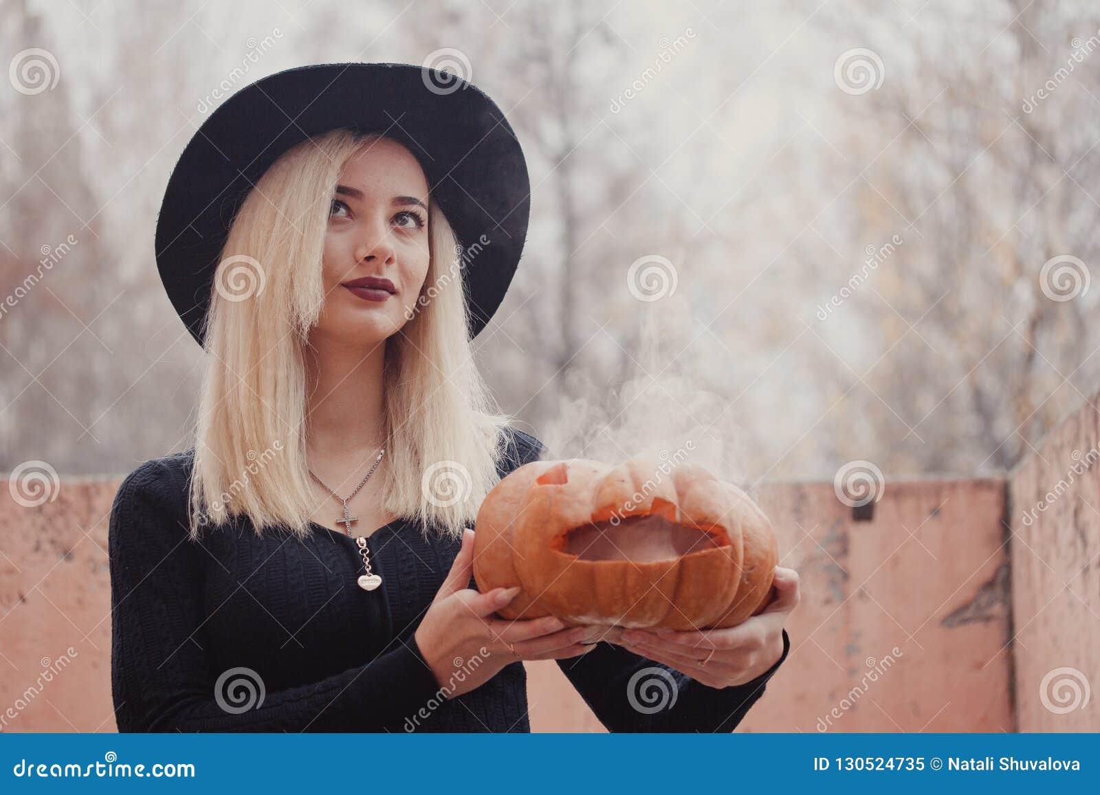 Młoda kobieta trzyma Halloween dyniowy z wewnątrz go w jesieni w czarnym żakiecie z białym dymnym przybyciem