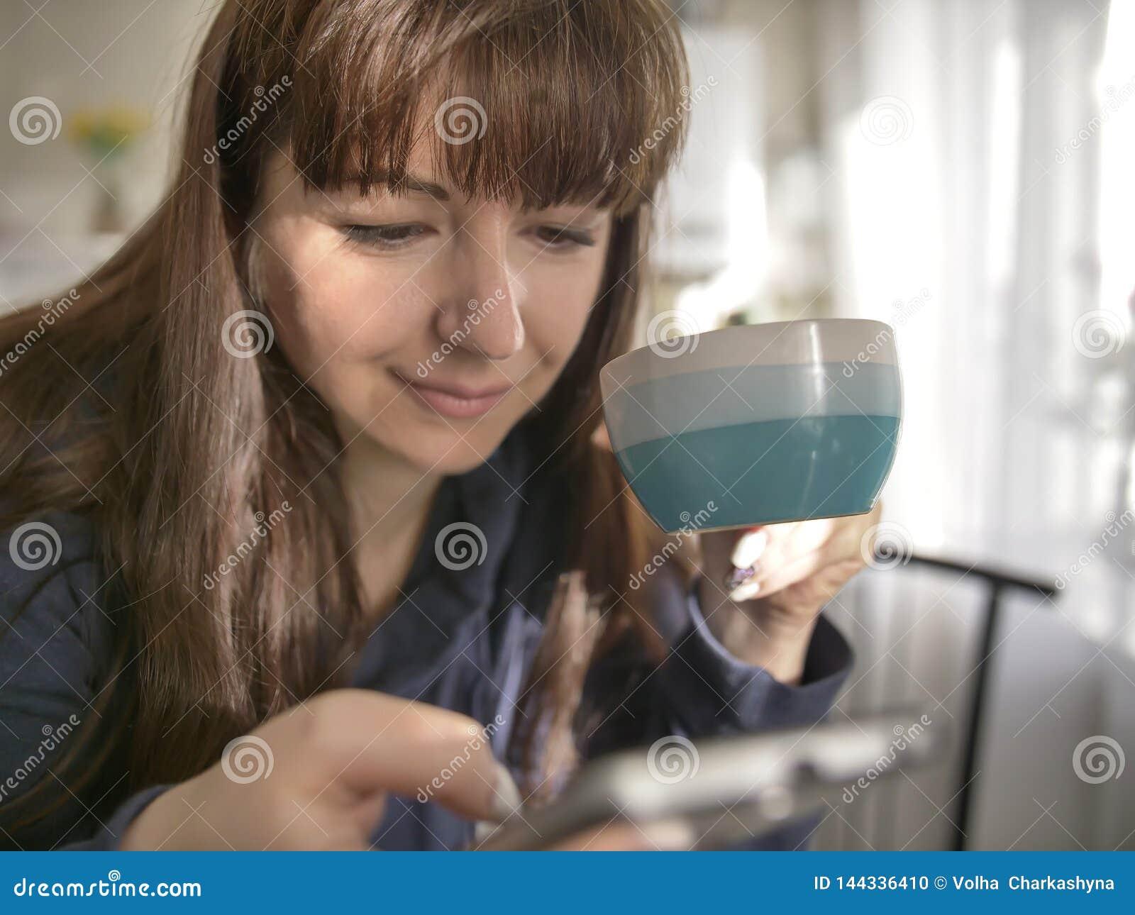 Młoda kobieta trzyma kawowego kubek i używa telefon w kuchni