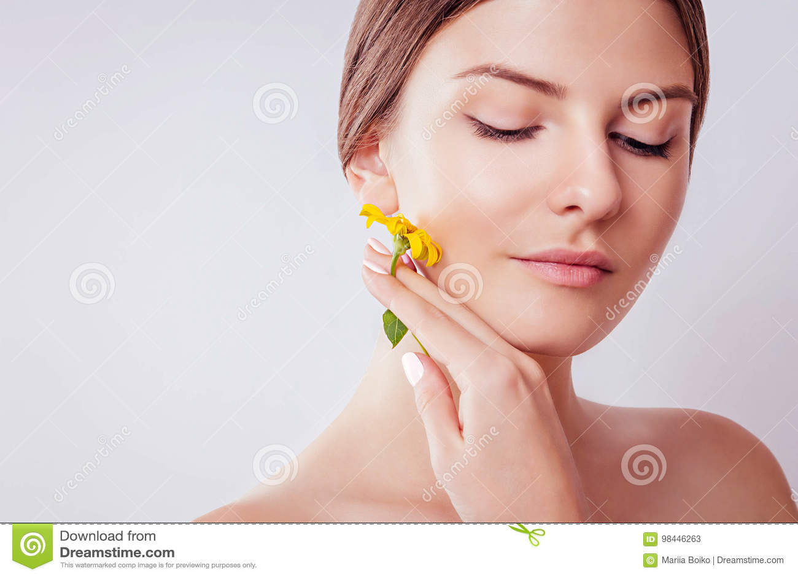 Młoda kobieta trzyma kwiatu z naturalnym makeup Organicznie kosmetyka pojęcie