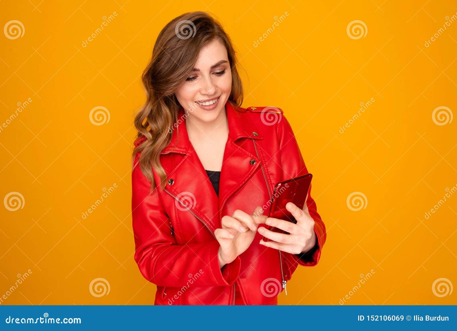 Młoda kobieta trzyma mobilny i patrzeje na mnie w czerwieni ubraniach odizolowywał