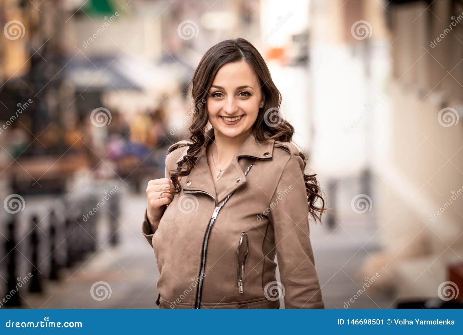 Młoda kobieta uśmiecha się szczęśliwego w ulicie