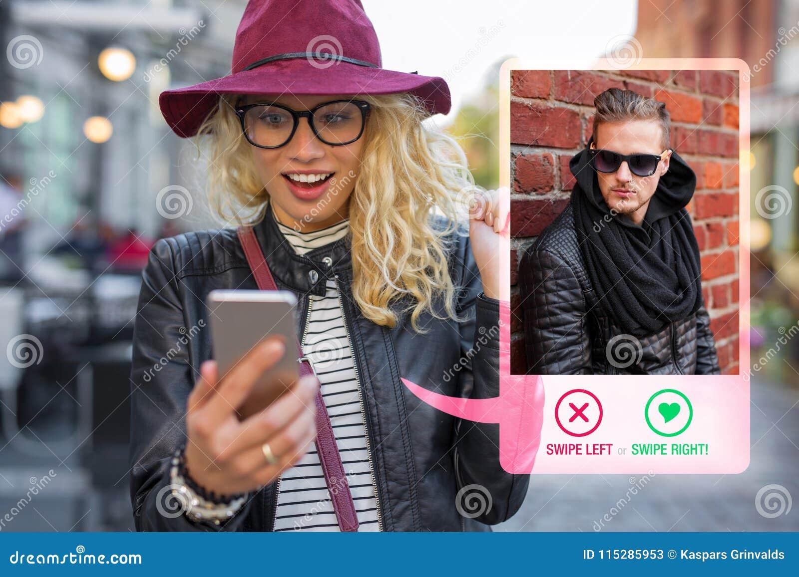 Młoda kobieta używa datujący app na telefonie komórkowym