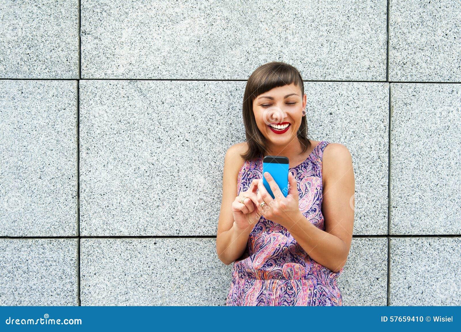 Młoda kobieta używa jej wiszącą ozdobę w miasta ono uśmiecha się