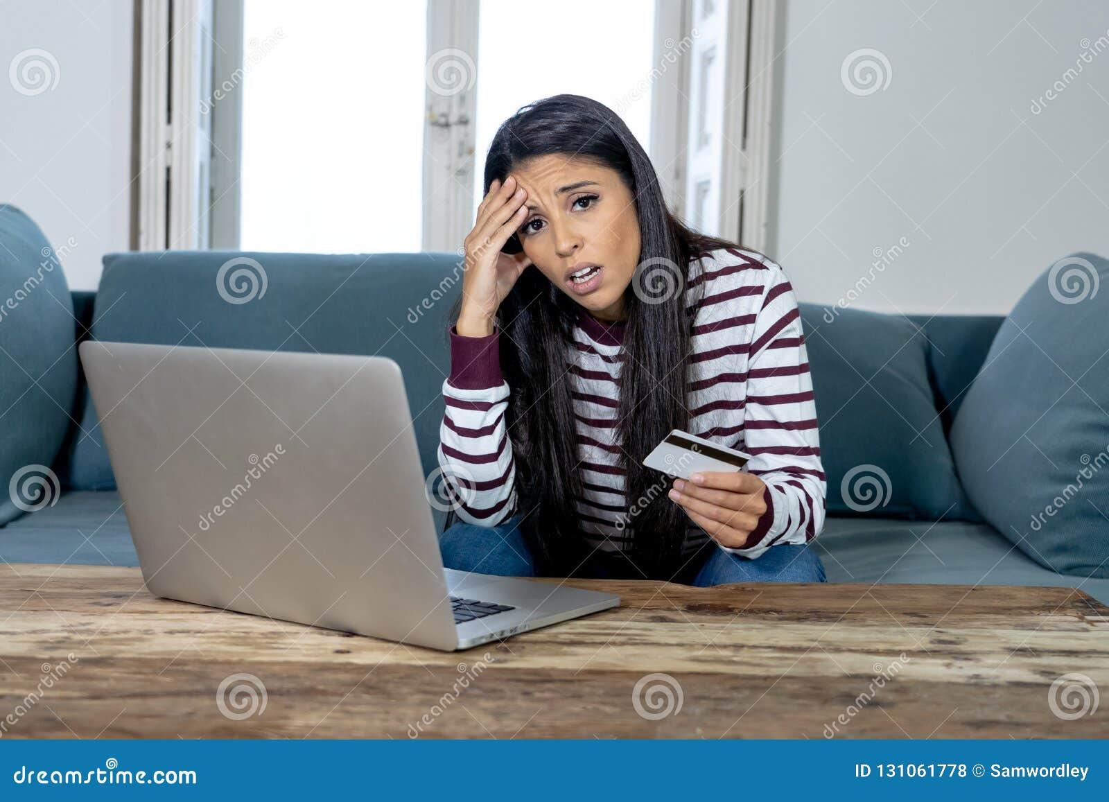 Młoda kobieta używa laptop gniewnego i zaakcentowanego o jej kredytowej karty rachunku