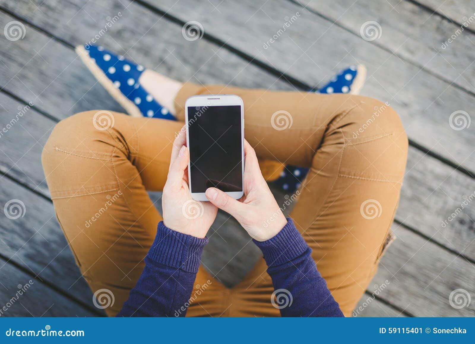 Młoda kobieta używa mądrze telefon