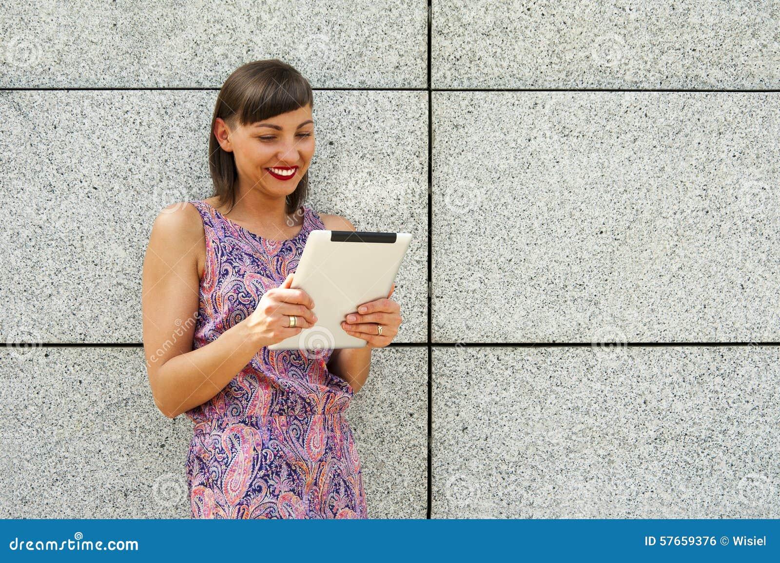 Młoda kobieta używa pastylki pozycję przeciw ścianie w mieście