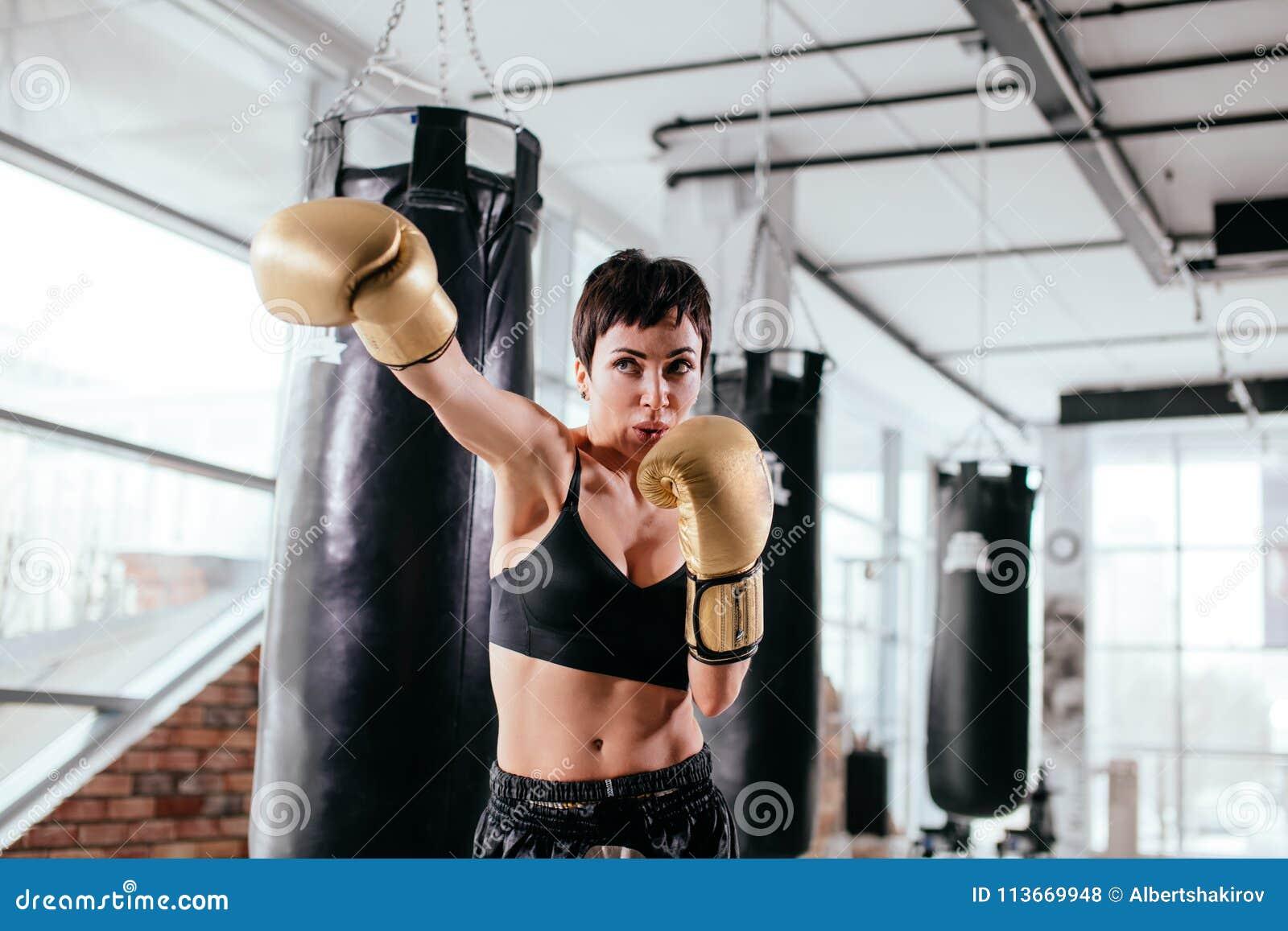 Młoda kobieta uderza gwałtownego cios z chronienie rękawiczkami z sporty spojrzeniem