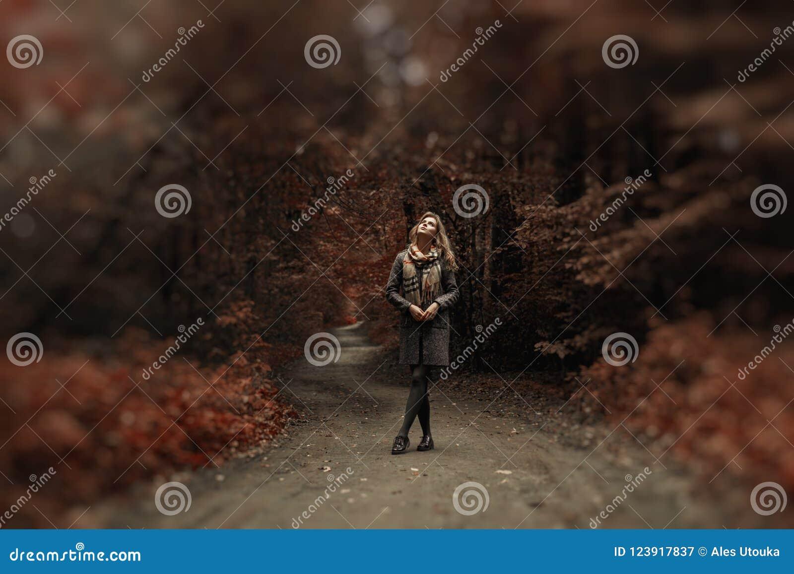Młoda kobieta w żakiecie i szalik chodzimy w zadziwiającym parku