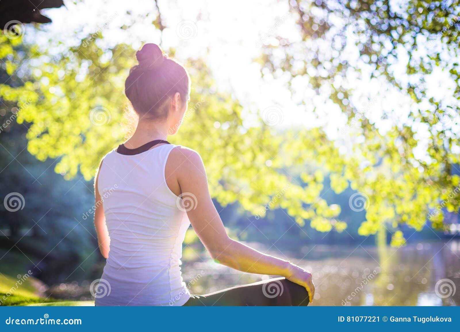 Młoda kobieta w bielu odgórny ćwiczy joga w pięknej naturze Medytacja w ranku słonecznym dniu
