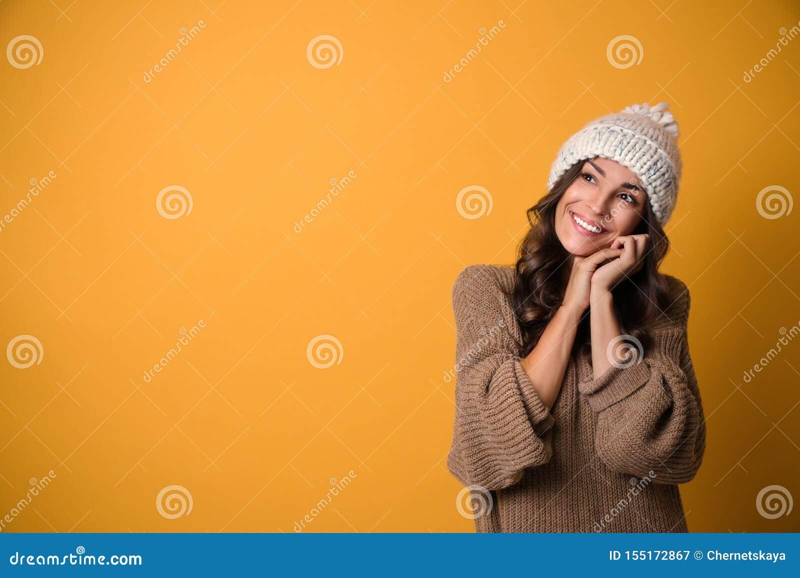 Młoda kobieta w ciepłym pulowerze i kapeluszu na żółtym tle Bo?e Narodzenie sezon