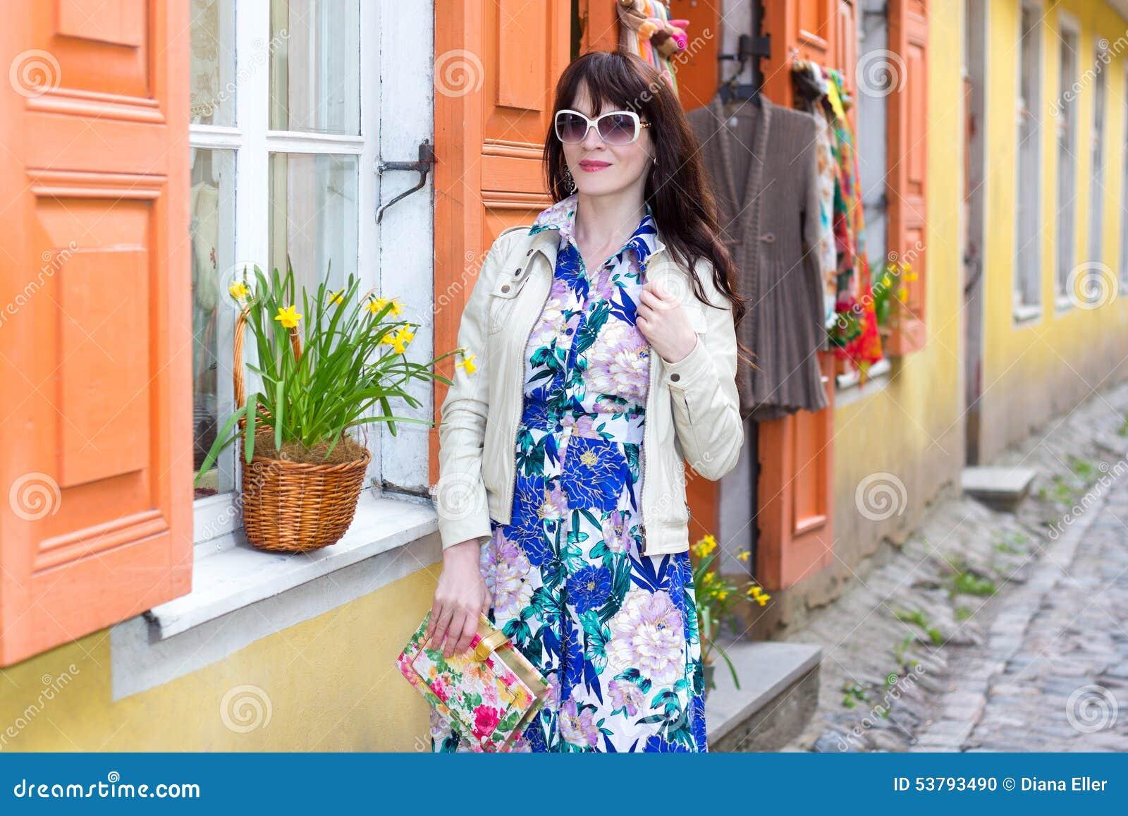 Młoda kobieta w długim smokingowym odprowadzeniu w starym miasteczku