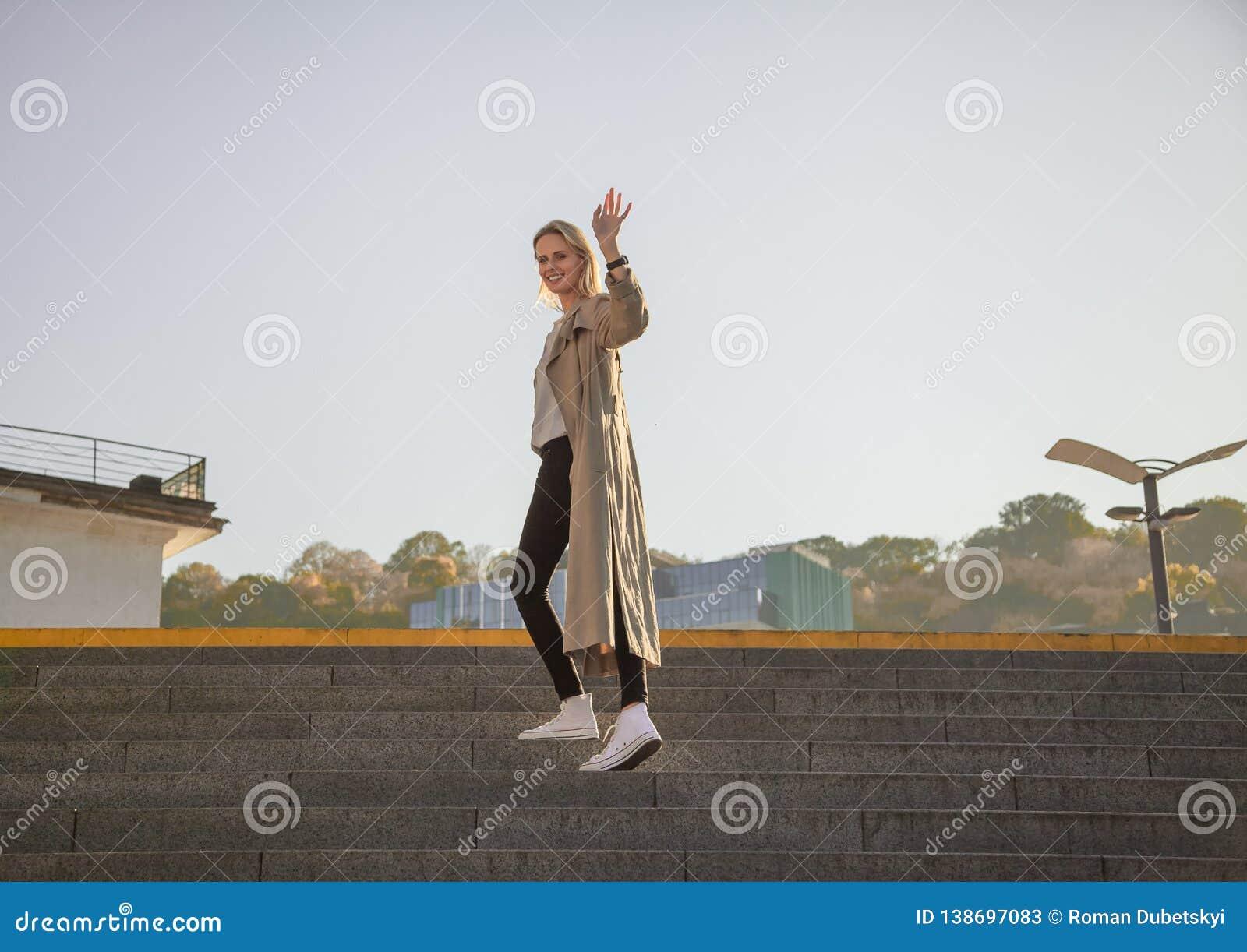 Młoda kobieta w eleganckim wiosna żakiecie w modnych szkłach w białej koszulce w czarnym rzemiennym torebki odprowadzeniu wzdłuż