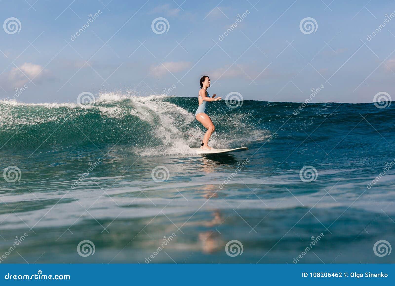 Młoda kobieta w jaskrawym bikini surfingu na desce w oceanie