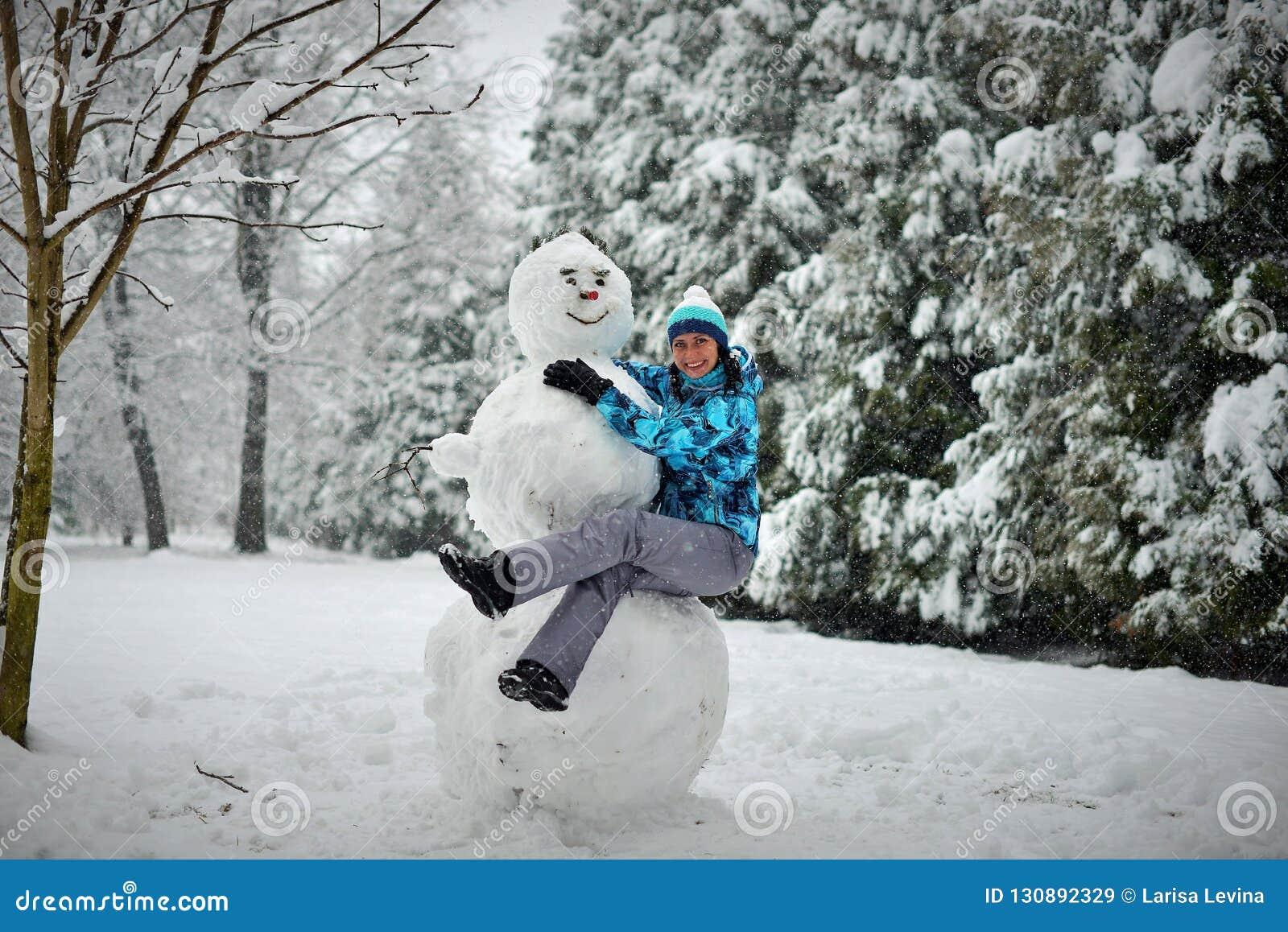Młoda kobieta w lesie w zimie ściska dużego bałwanu