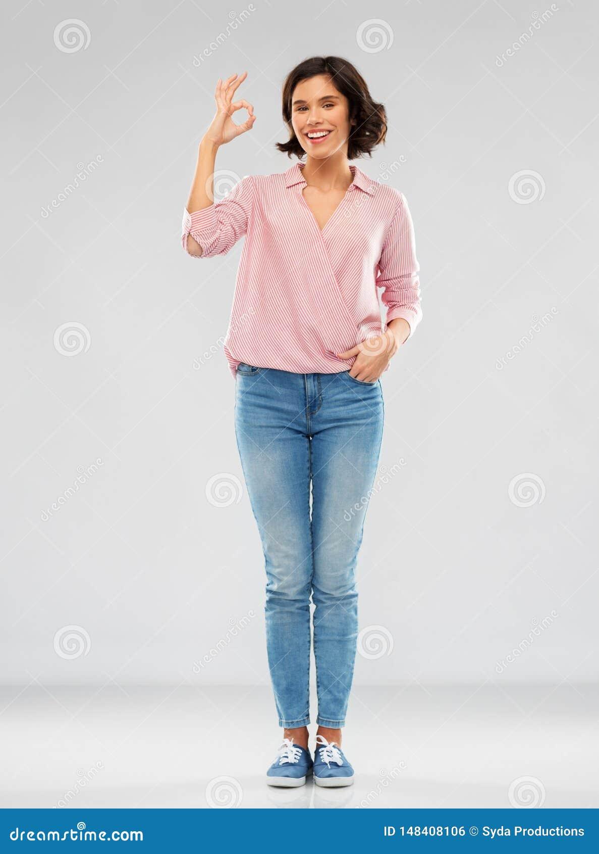 Młoda kobieta w pasiastej koszula i cajgach pokazuje ok