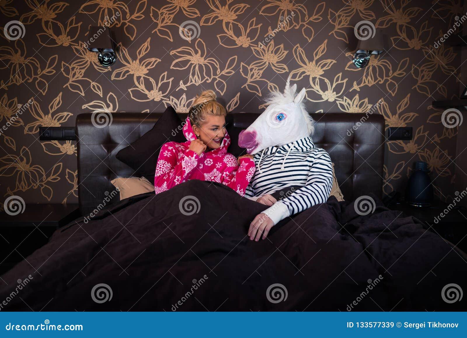 Młoda kobieta w piżamie siedzi na łóżku z jednorożec