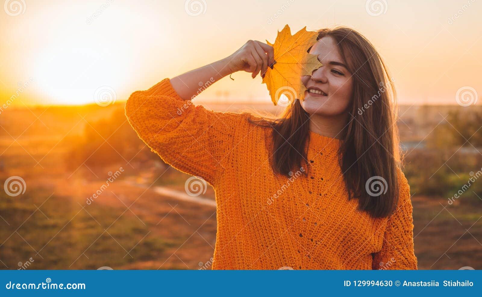Młoda kobieta w pomarańczowym pulowerze z z żółtymi liśćmi, plenerowy portret w miękkim pogodnym świetle dziennym Jesień Zmierzch