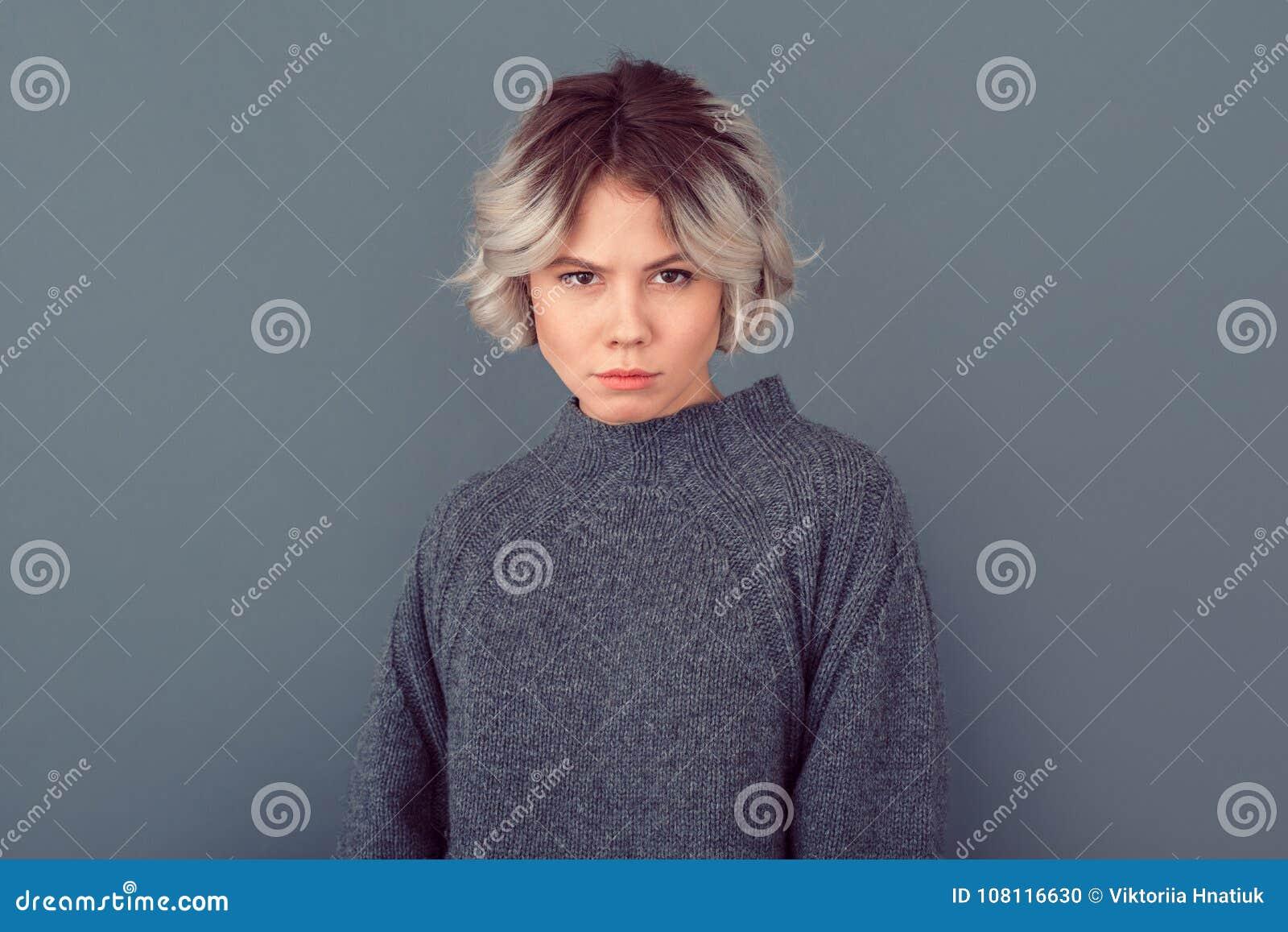Młoda kobieta w popielatego puloweru pracownianym obrazku na popielatym tle ostrożnym