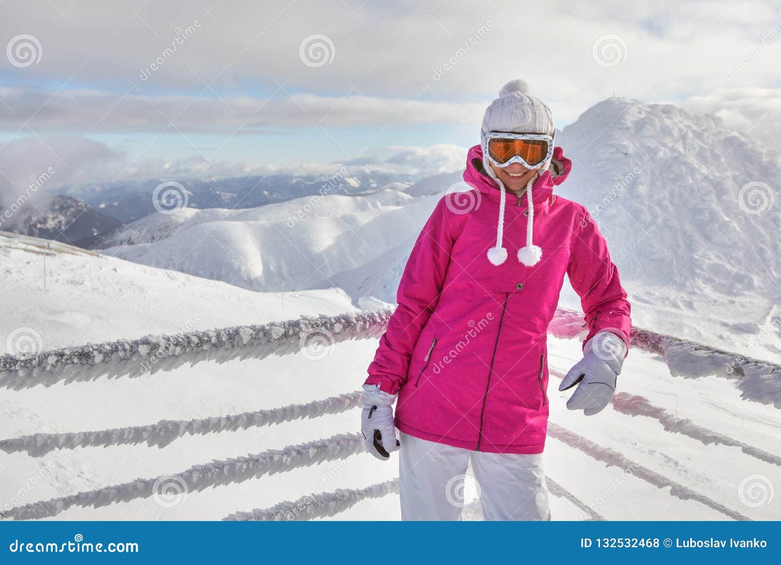 Młoda kobieta w różowej kurtce, będący ubranym narciarskich gogle, opiera na śniegu
