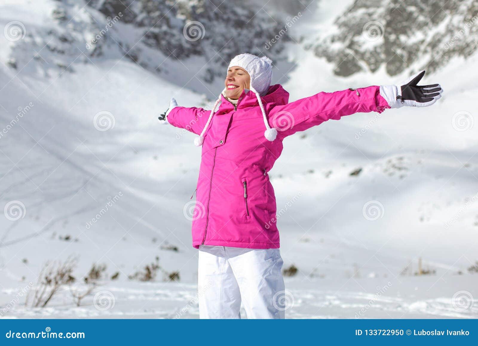 Młoda kobieta w różowej narciarskiej kurtce, rękawiczkach i spodniach, ręki rozprzestrzenia, e
