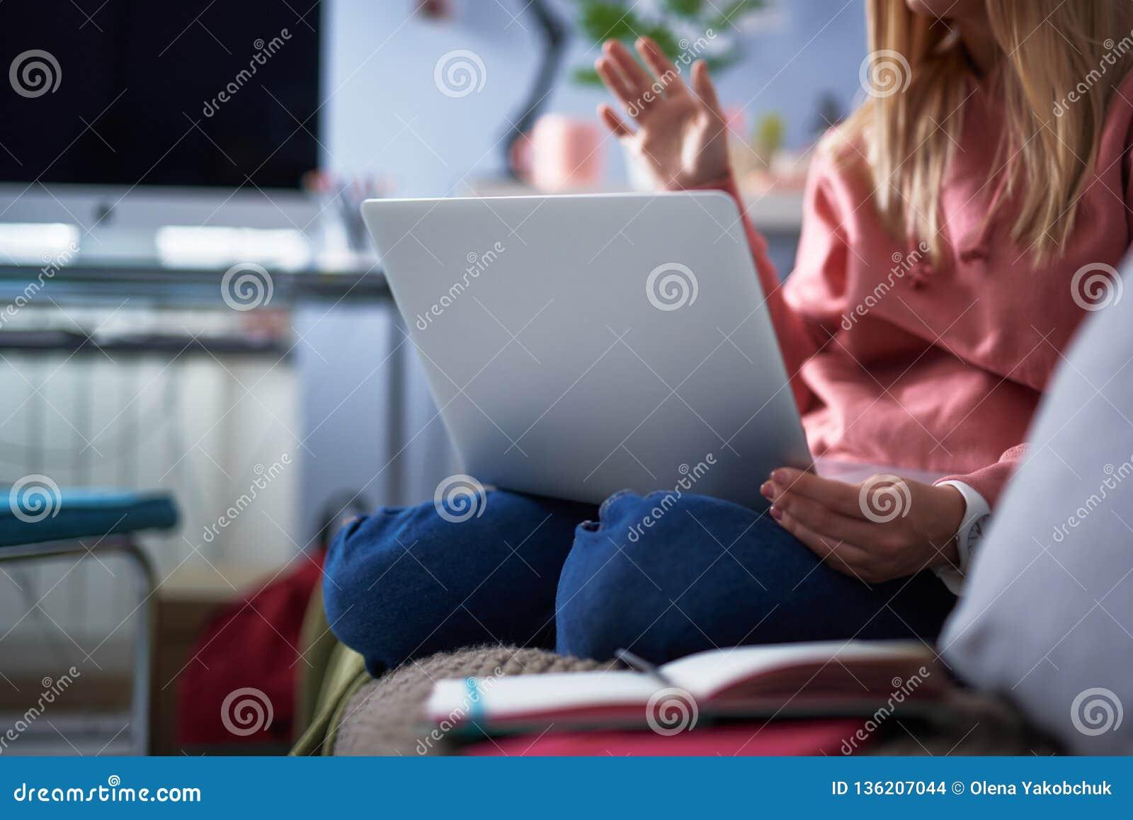 Młoda kobieta w różowym hoodie używać laptop