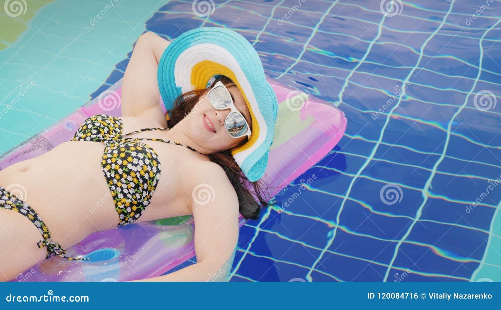 Młoda kobieta w słońc szkłach garbnikuje na nadmuchiwanej materac, pływa w basenie
