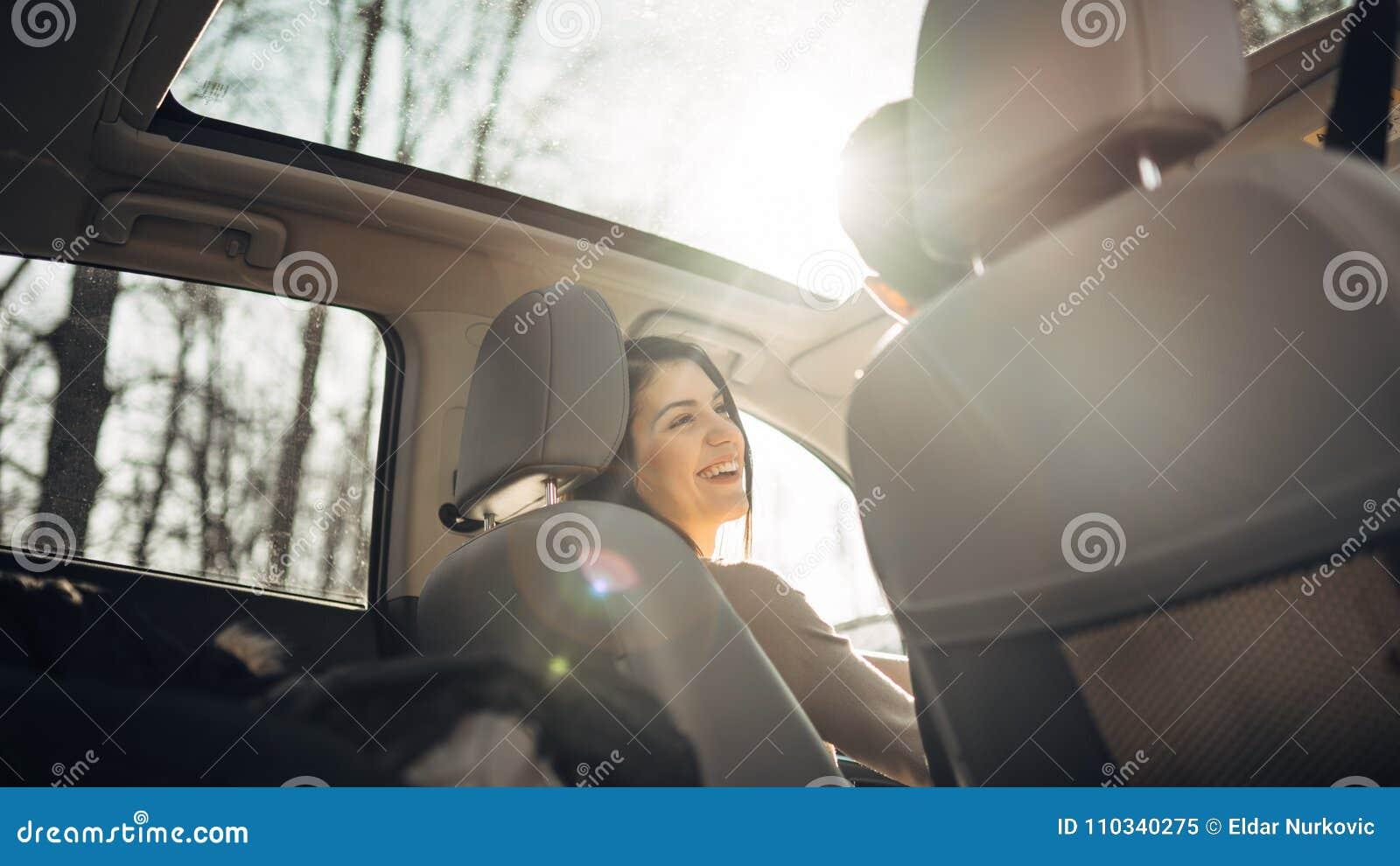 Młoda kobieta w samochodzie, żeński kierowca patrzeje ono uśmiecha się i pasażera Cieszyć się przejażdżkę, podróżuje, wycieczki s