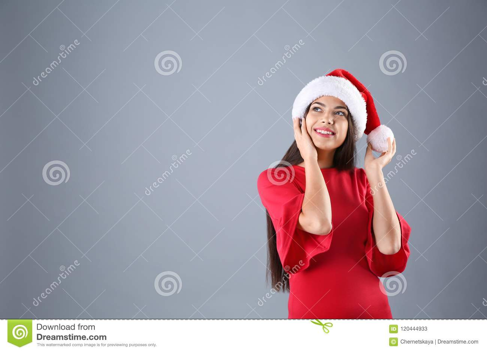 Młoda kobieta w Santa kapeluszu na popielatym tle świętuje świętowania bożych narodzeń córki kapeluszy macierzysty Santa target27