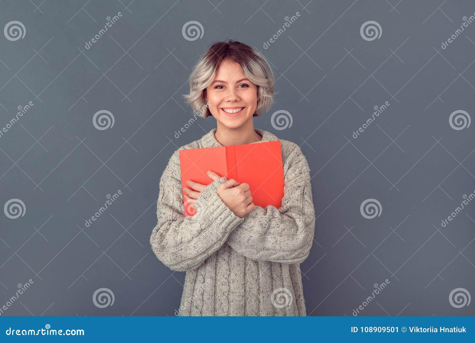 Młoda kobieta w woolen pulowerze odizolowywającym na popielatej ściennej zimy pojęcia powieści książce