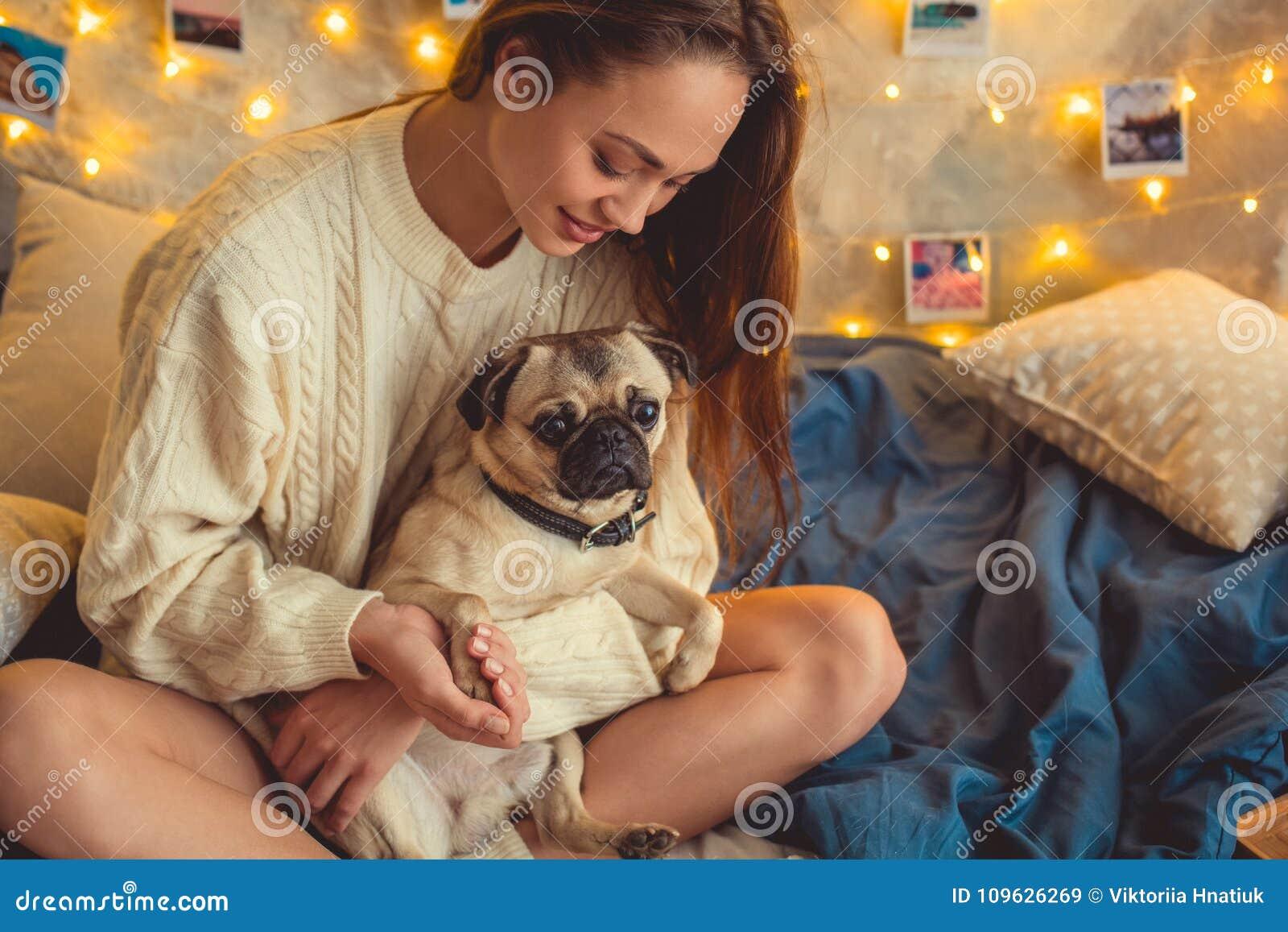 Młoda kobieta weekend w domu dekorował sypialni mienia łapę pies