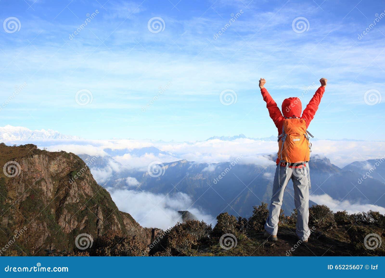 Młoda kobieta wycieczkowicza otwarte ręki przy halnym szczytem