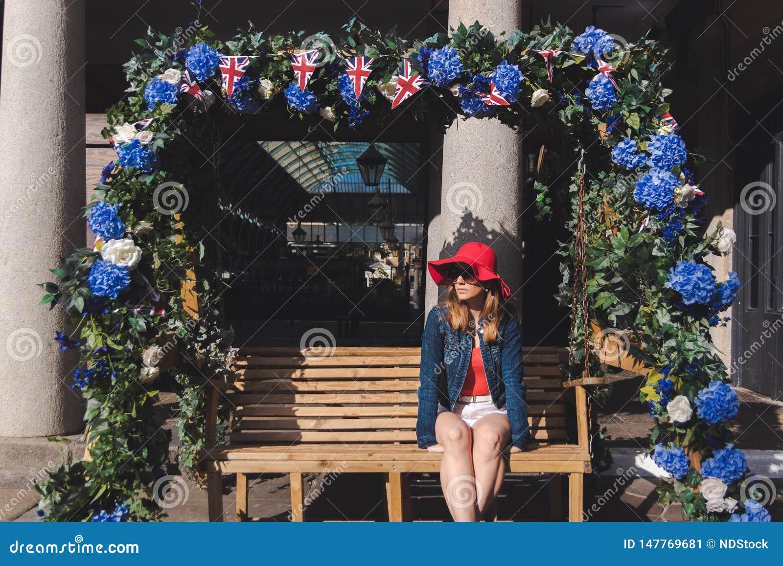 Młoda kobieta z czerwonym kapeluszem sadzającym na kołyszącej ławce w Londyn