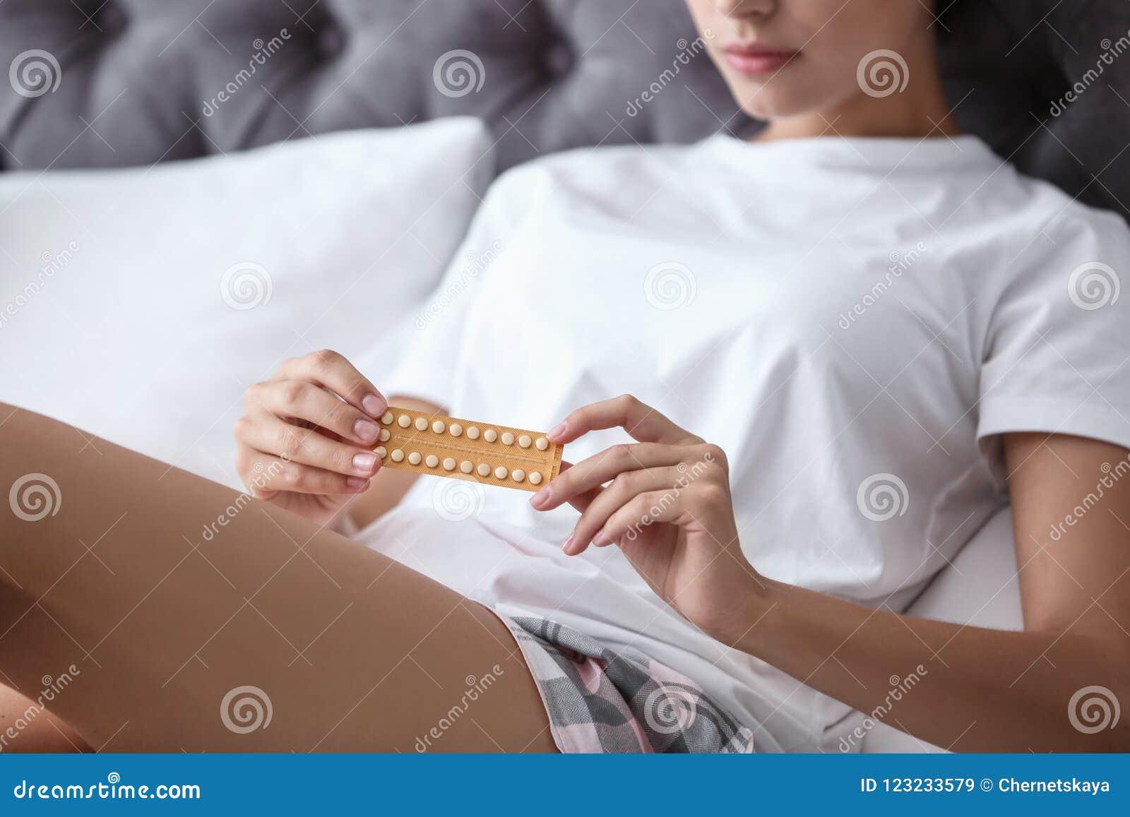 Młoda kobieta z kontrola urodzin pigułkami w sypialni