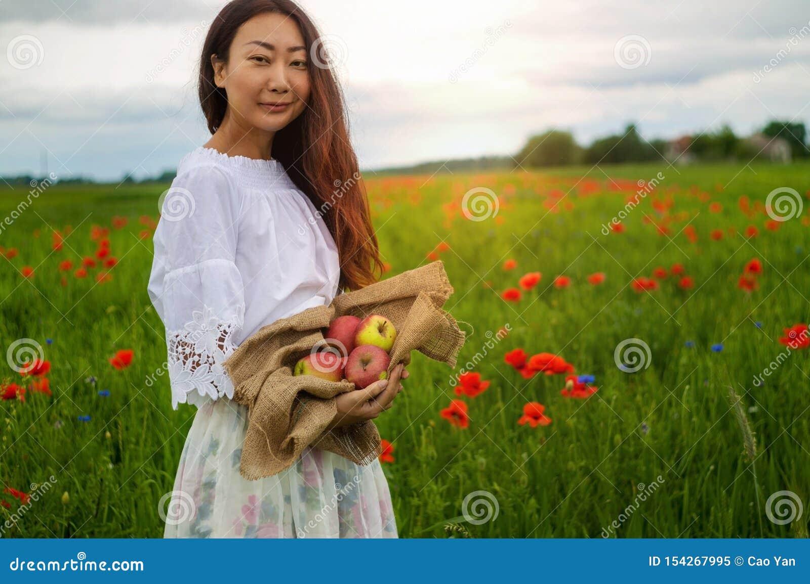 Młoda kobieta z koszem świeżo ukradzeni jabłka w polu