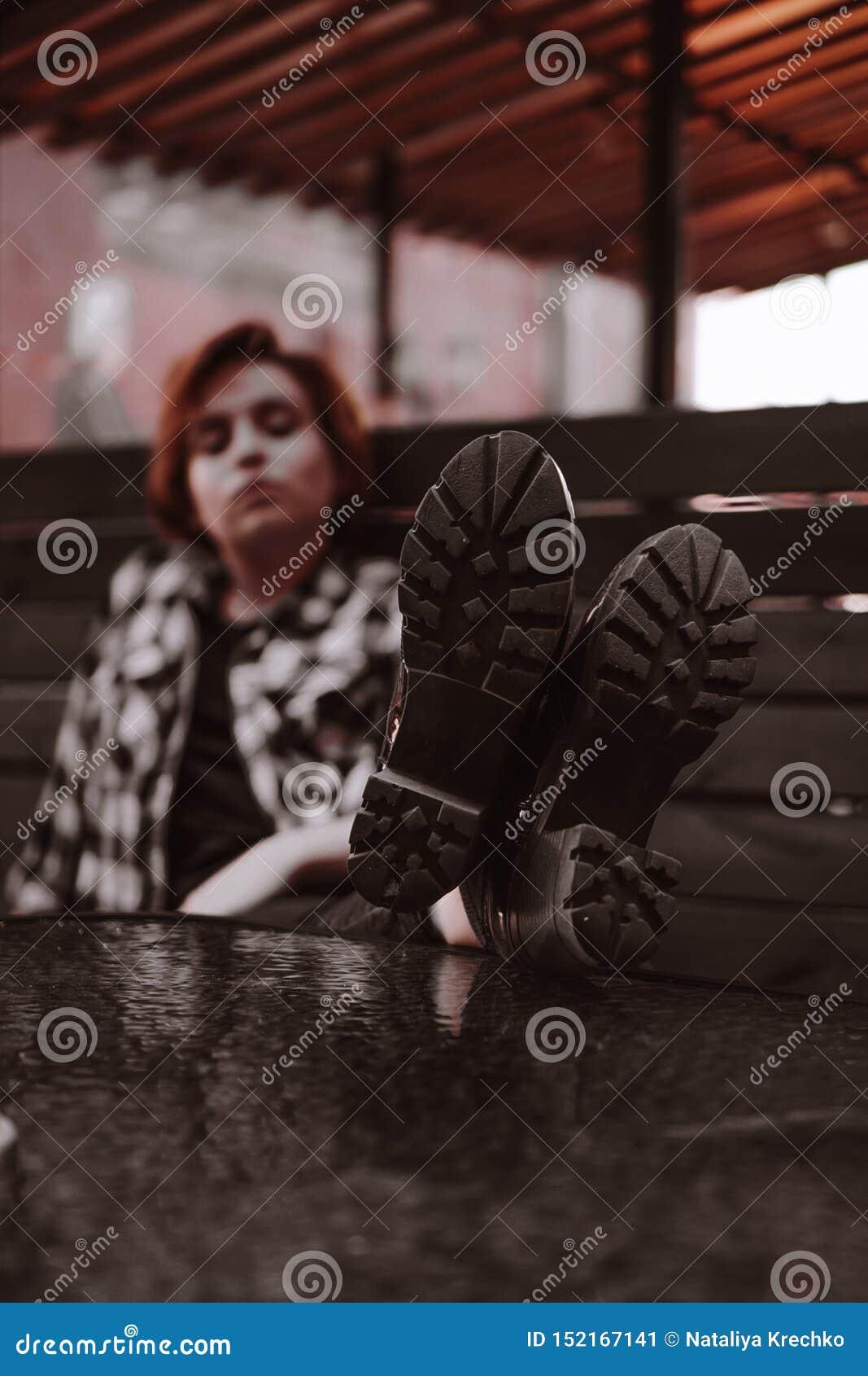 Młoda kobieta z krótkim czerwonym włosy w barze stawia ona nogi na stole