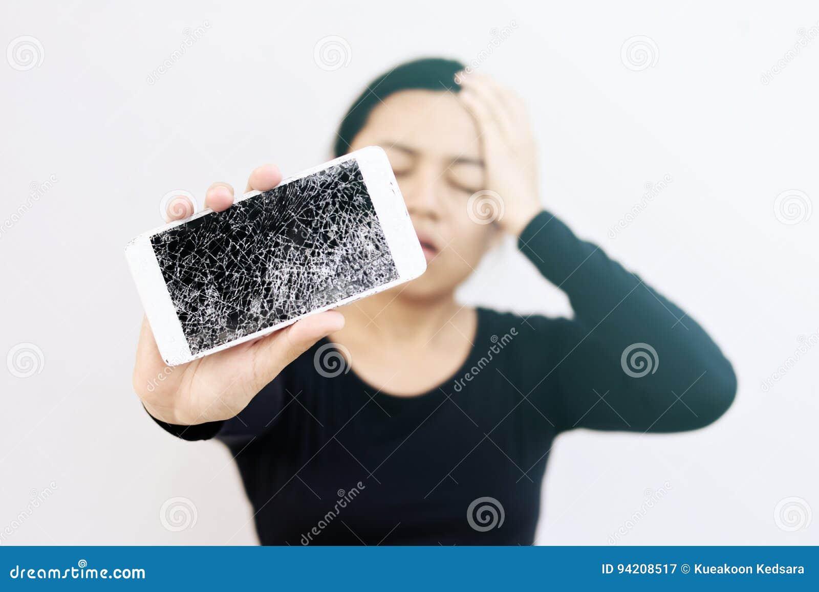 Młoda kobieta z skołatanym wyrażeniowym mieniem jej łamany telefon