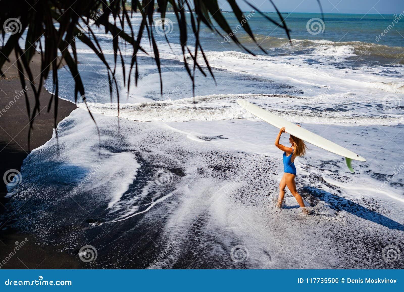 Młoda kobieta z surfboard spacerem na czarnej piasek plaży
