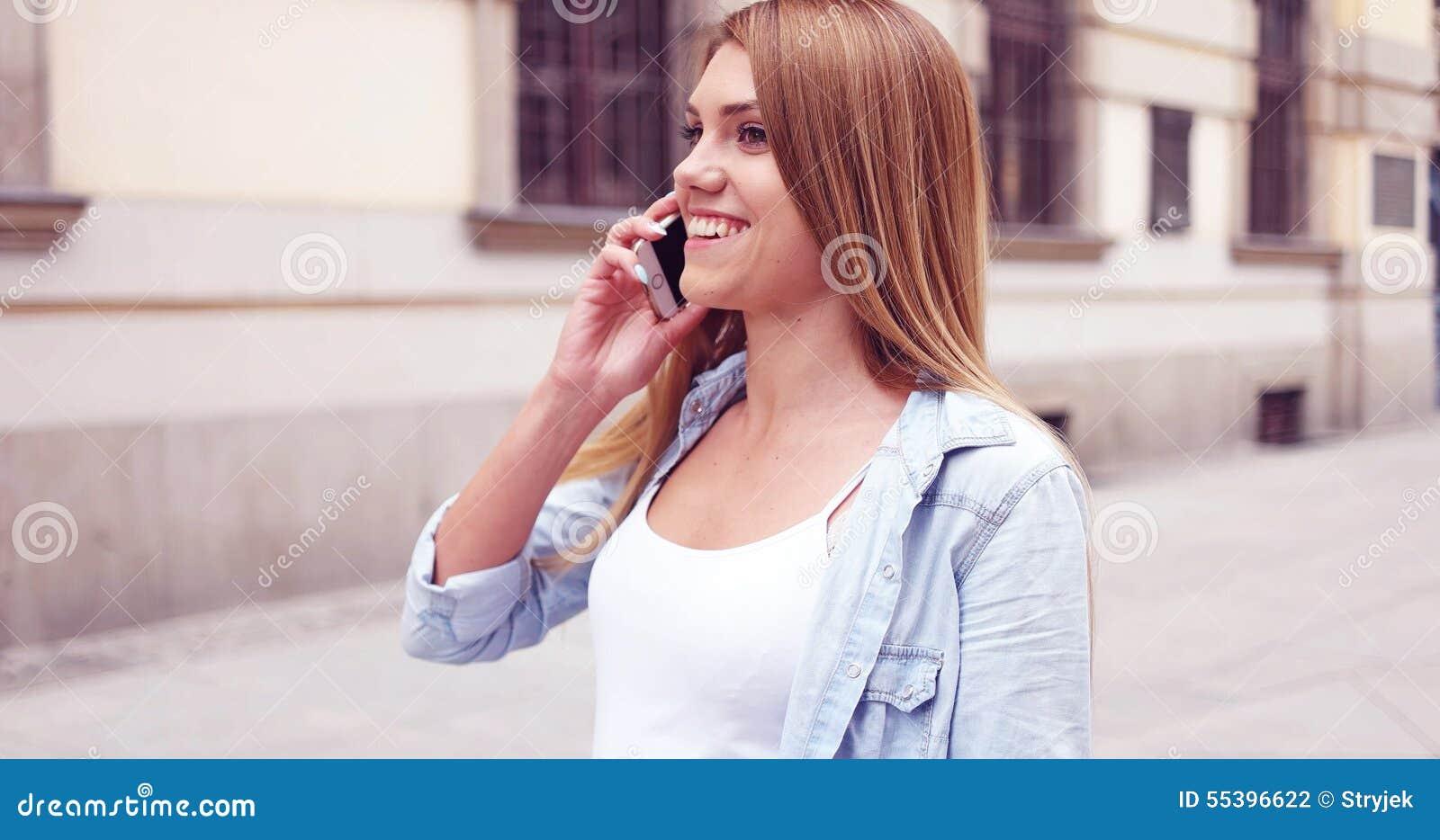 Młoda Kobieta z telefonu odprowadzeniem przy ulicą