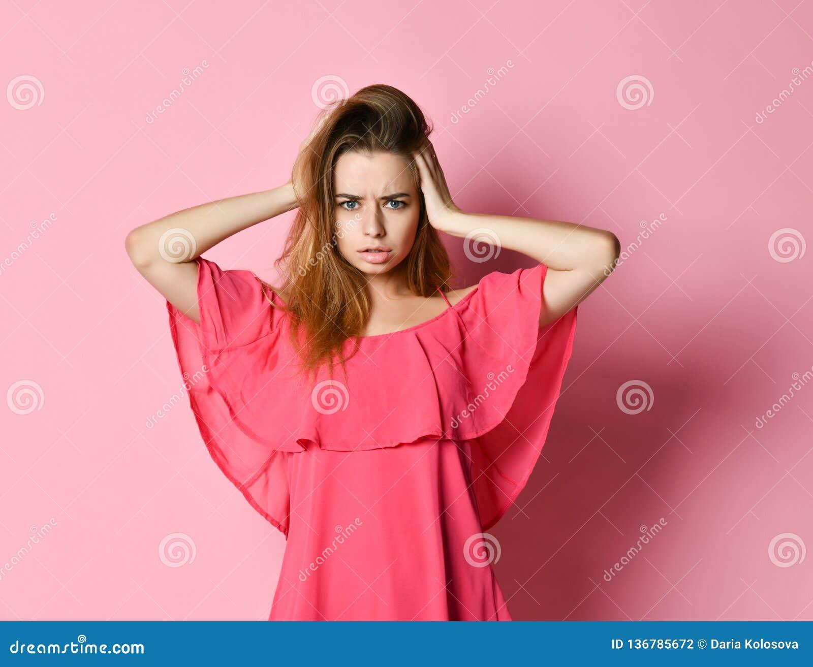 Młoda kobieta z uczciwym włosy w menchii smokingowej marszczy brwi chwyta głowie