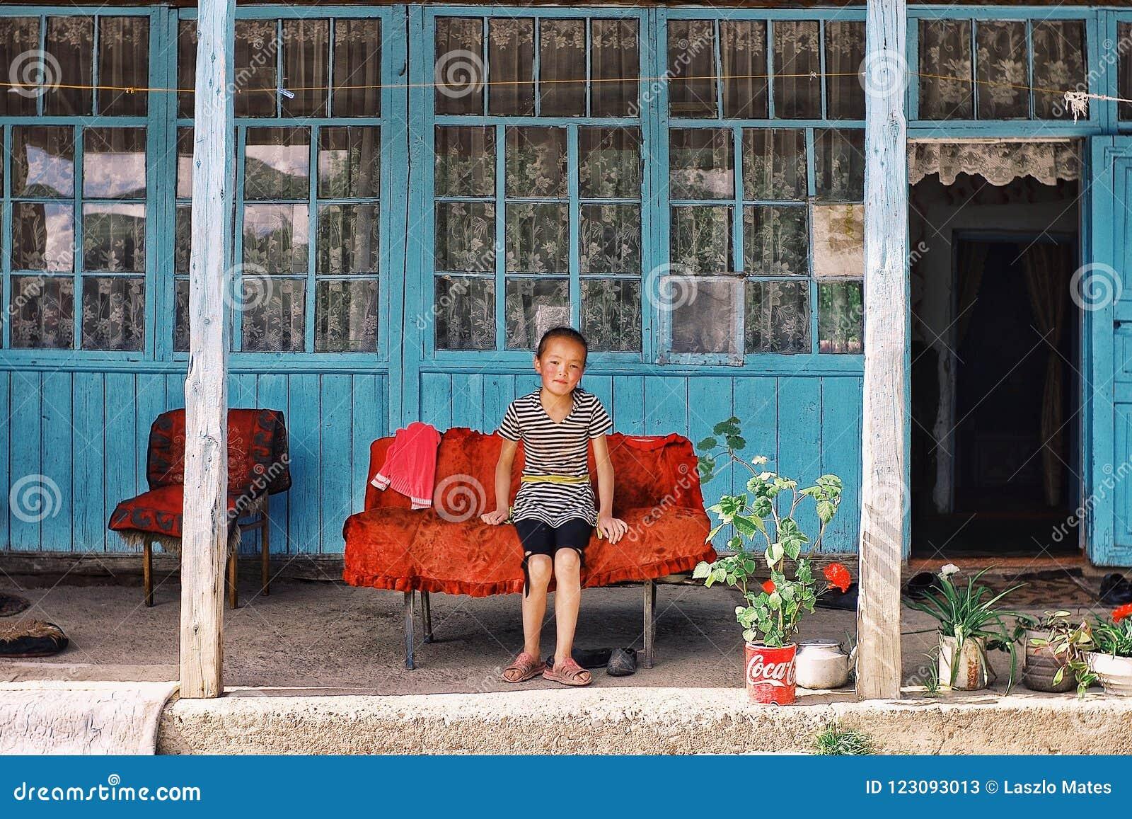Młoda lokalna wioski dziewczyna ma odpoczynek podczas popołudnia przed ich tradycyjną górą
