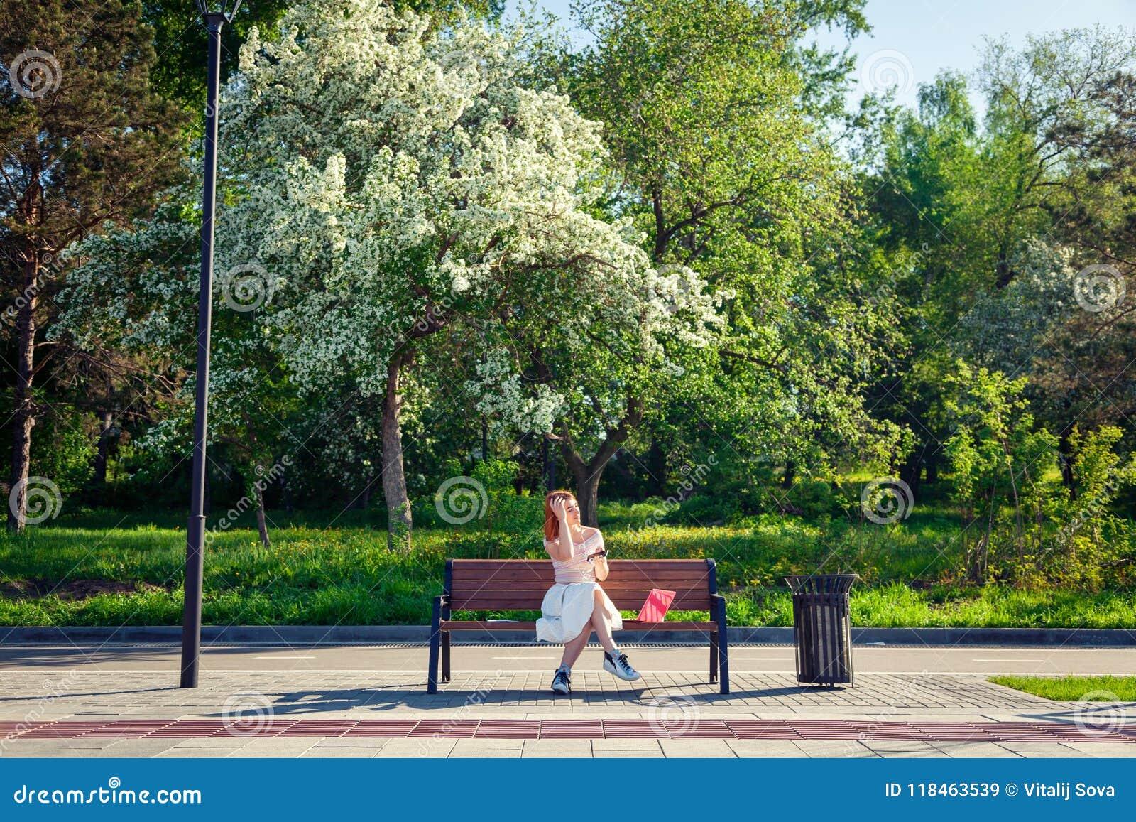 Młoda miedzianowłosa kobieta w parku