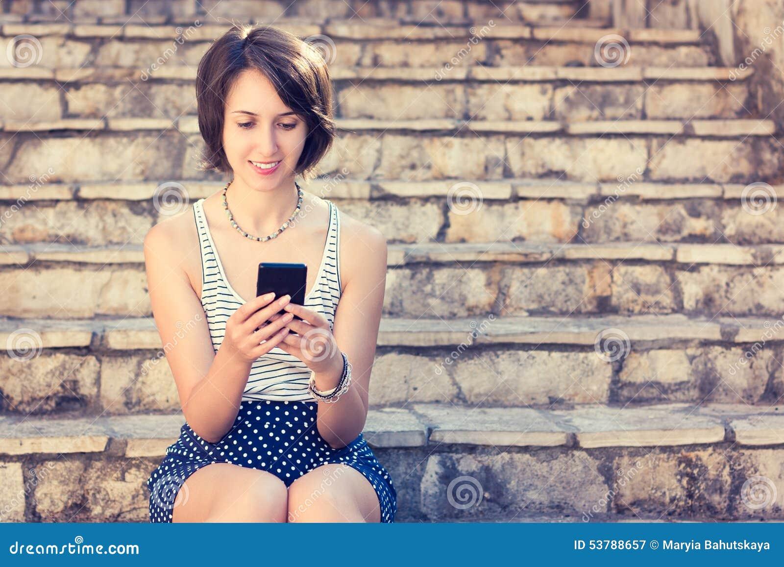 Młoda modniś dziewczyna Texting z Jej telefonem komórkowym