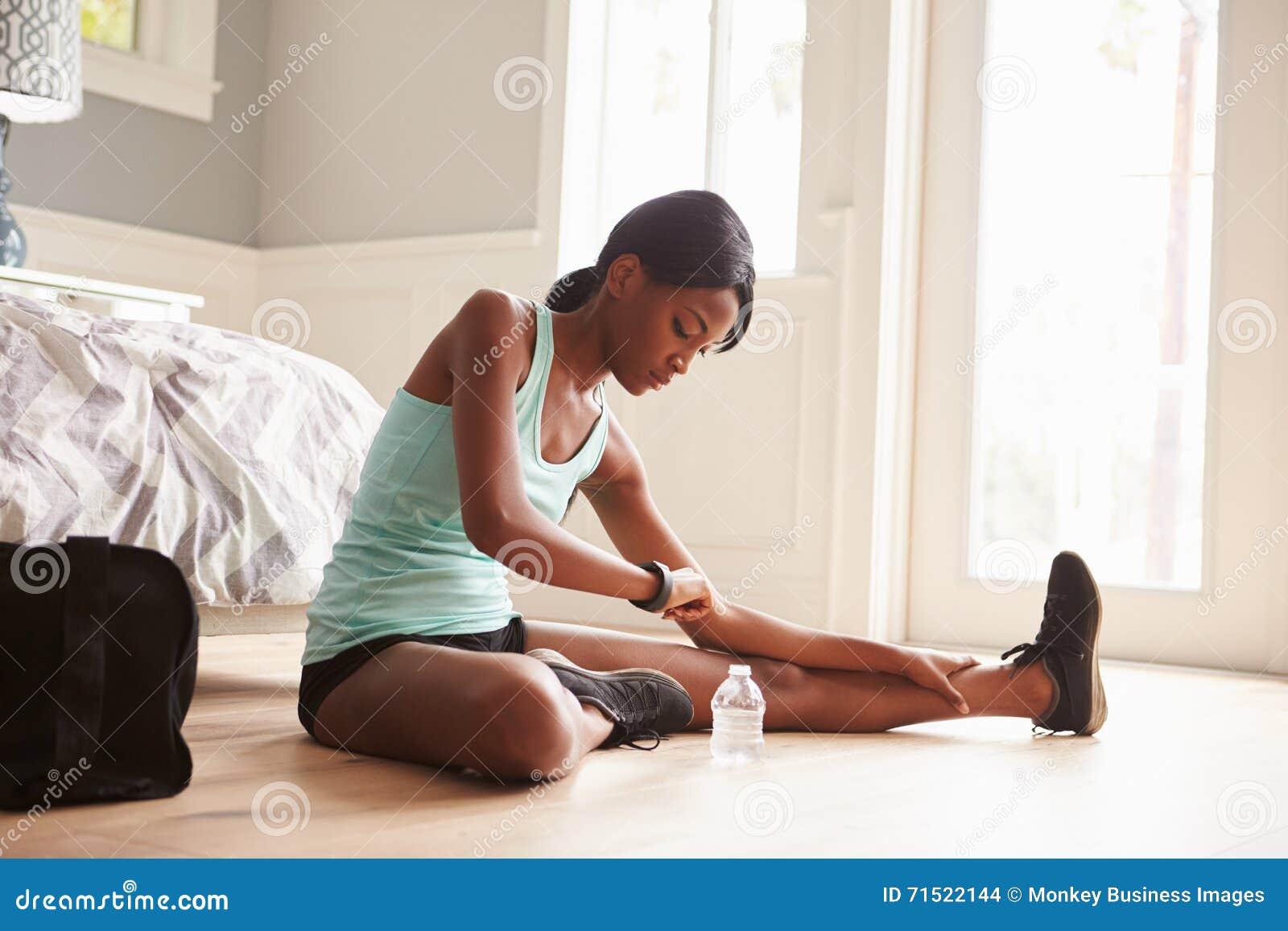 Młoda murzynka używa mądrze zegarek podczas gdy ćwiczący w domu