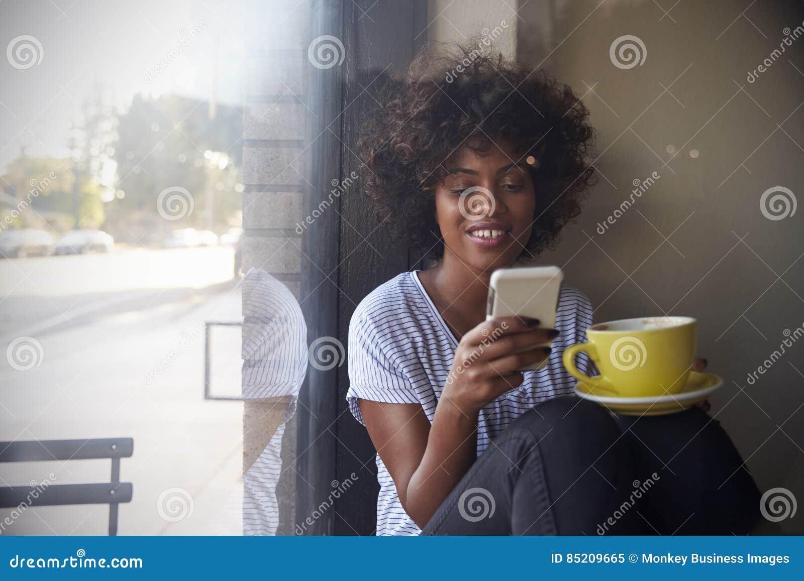 Młoda murzynka używa smartphone obok okno w kawiarni